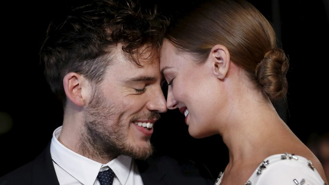 """Actor Sam Claflin and partner Laura Haddock pose for photographers on the red carpet at the UK premiere of """"The Hunger Games : Mockingjay Part 2"""" at Leicester Square in London, Britain November 5, 2015. REUTERS/Luke MacGregor"""